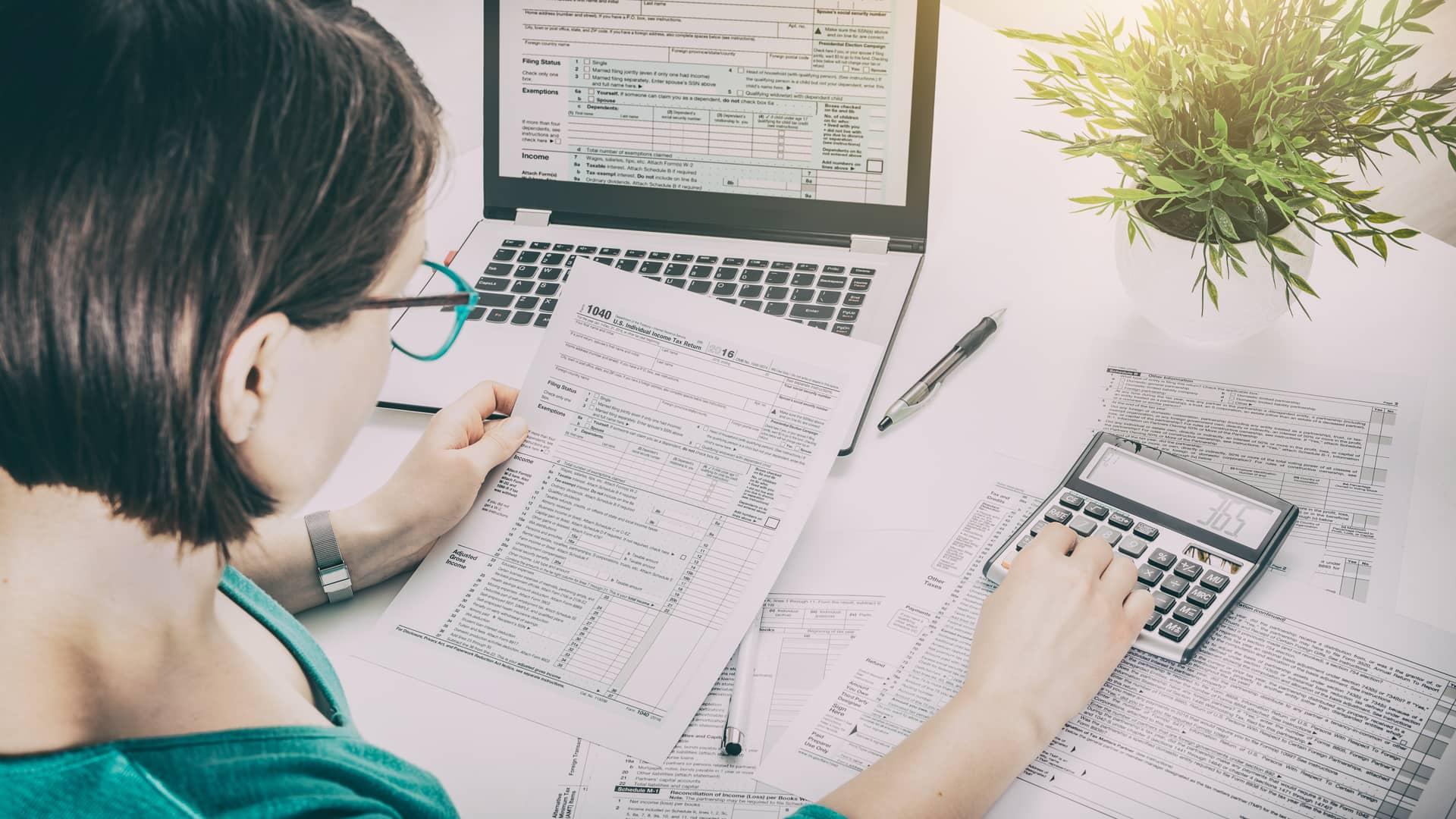 Mujer haciendo calculas de las fiscalidad de su inversión