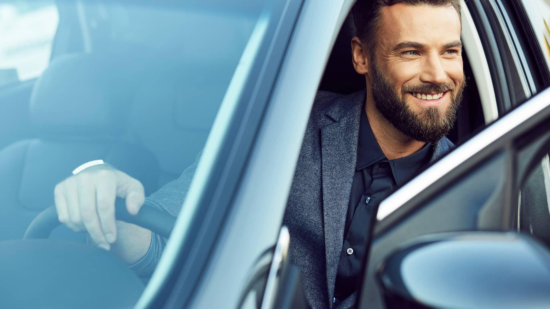 Joven sonriente en su nuevo coche simboliza préstamo coche