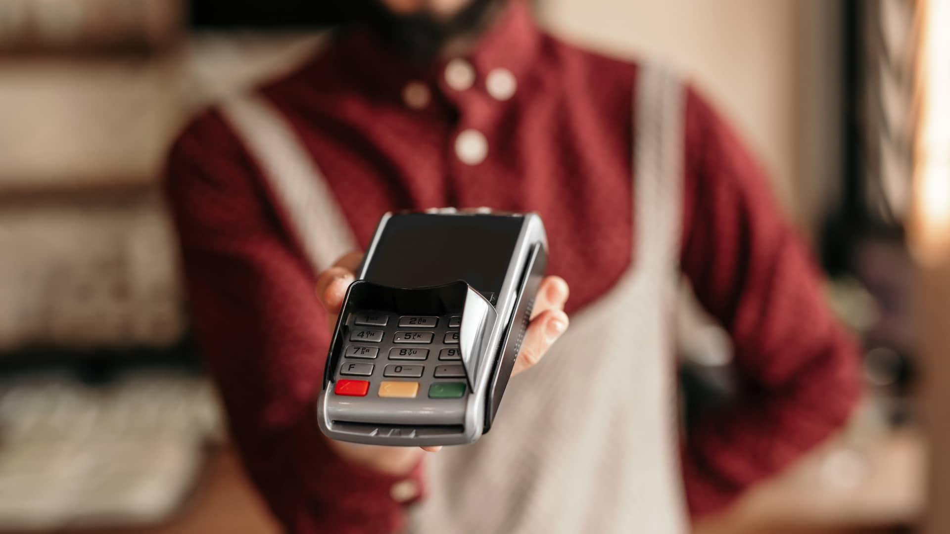 Joven ofreciendo datafono para realizar el pago con tarjeta contacless