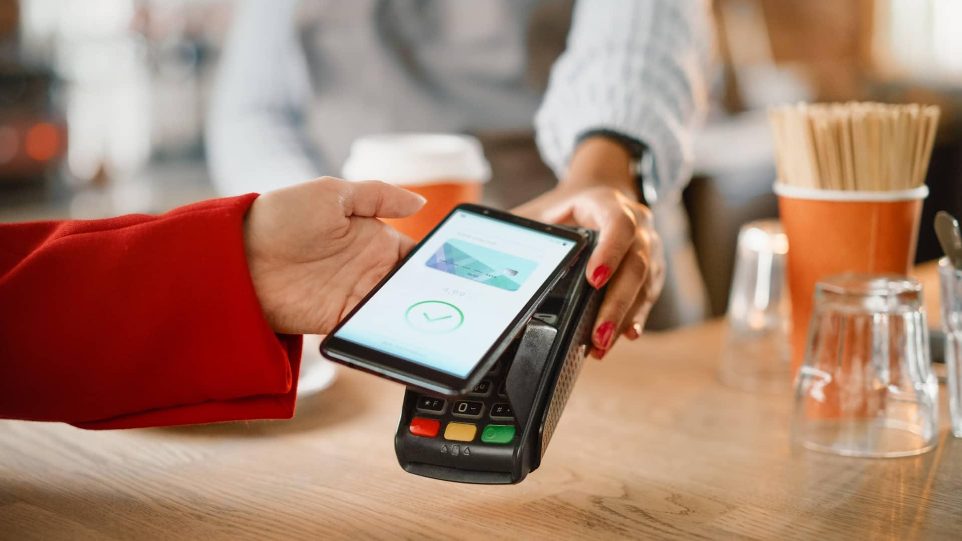 Mujer realizando pago con smartphone y recibiendo descuento de fidelización