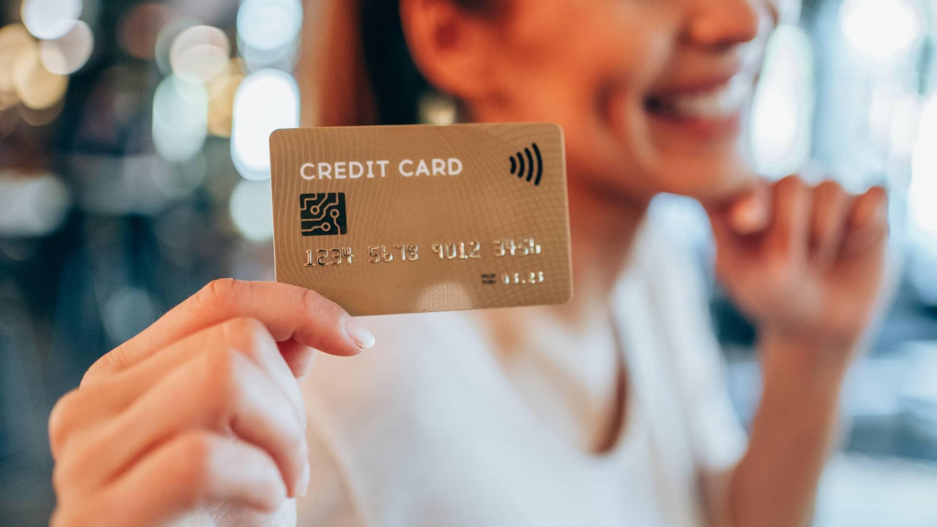 Joven sonriente sujetando tarjeta de crédito con la mano