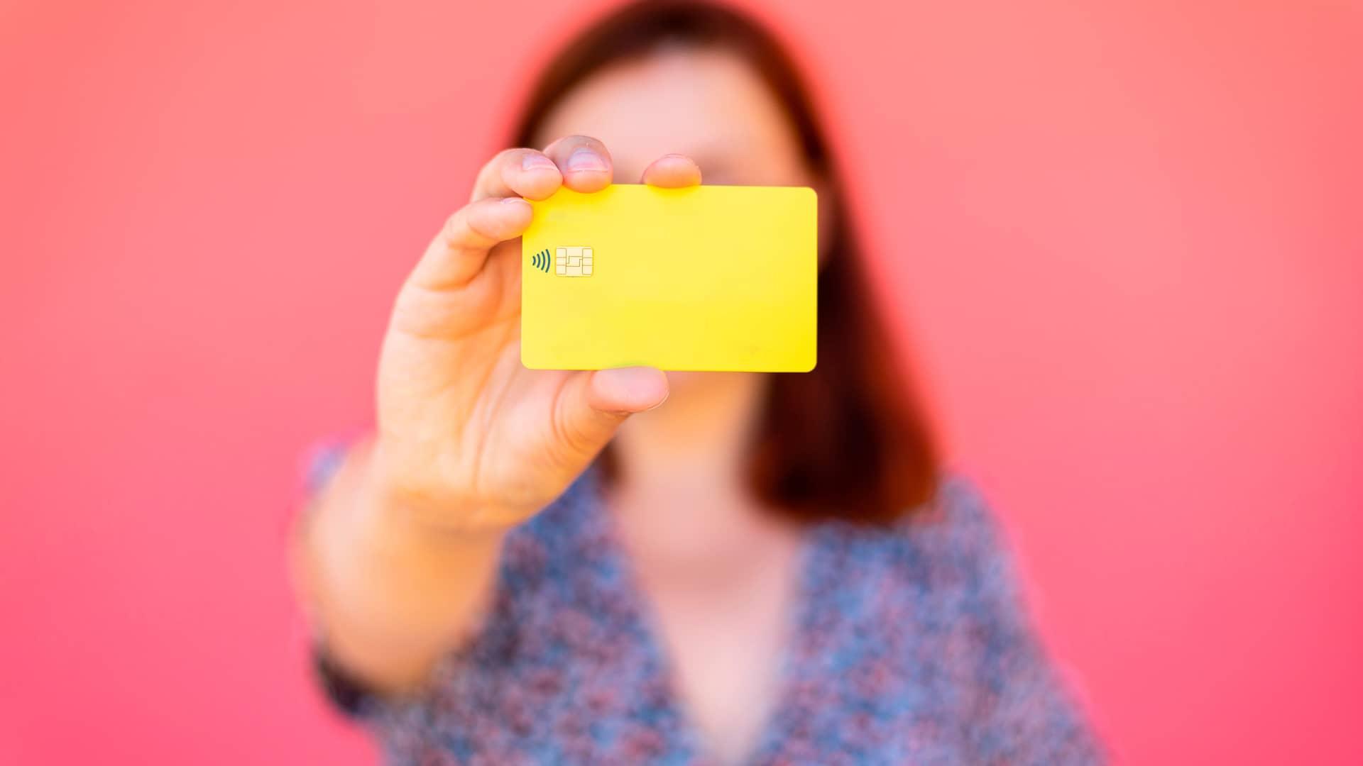 Mujer mostrando su tarjeta de débito