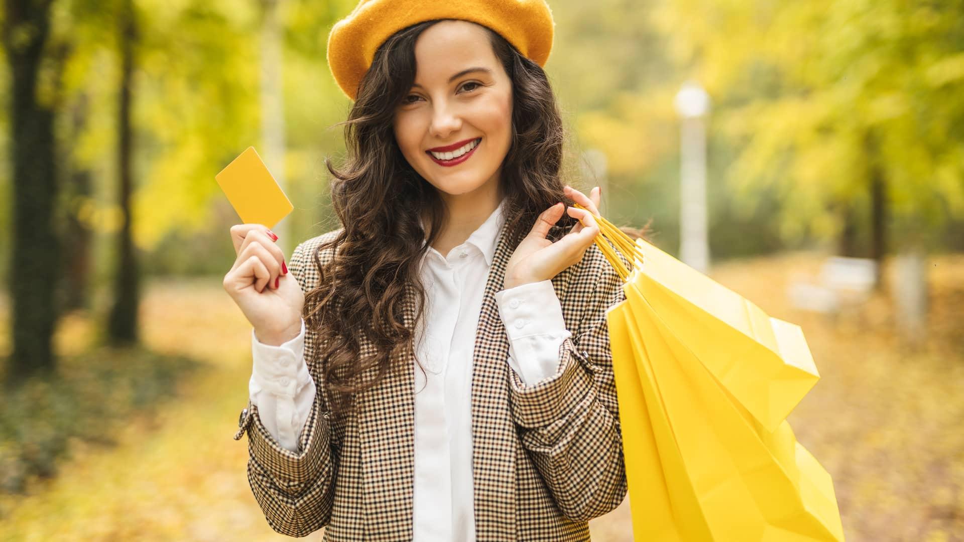Mujer sonriente volviendo de compras habiendo usado una tarjeta prepago